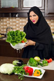 Arabian woman wearing holding a bowl of veggies in the kitchen Royalty Free Stock Photos