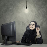 Arabian women and brilliant idea. Portrait of Arab business woman wearing glasses sitting and thinking of idea with under bright light bulb Stock Photos