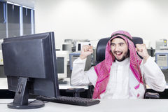 Arabian worker celebrates his success. Arabic businessman wearing islamic clothes in the office and celebrates his success with a computer on the table stock photos