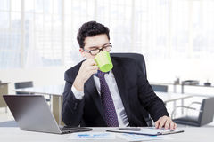 Arabian worker drinks coffee while working. Picture of Arabian businessman drinking a cup of coffee or tea while working in the office room Stock Photos