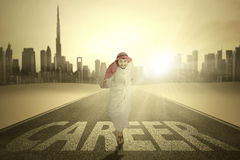 Arabian worker runs with Career word. Photo of Arabian young entrepreneur running on the street with Career word and smiling at the camera Stock Photos