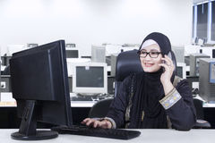 Arabian worker talking on the mobile phone. Pretty Arabian worker working in the office while wearing headscarf and talking on the mobile phone Royalty Free Stock Photos