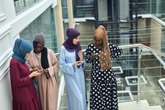 Arabian young women watching on cellphone musical video clip standing together. Arabian young fashionably dressed in muslim clothes women watching on cellphone stock images