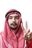 Arabian young man. Portrait of an arabian young man in traditional headscarf - shemagh. He shows peace sign by hand Stock Photo