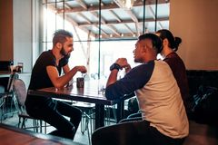 Arabian young men hanging in loft cafe. Middle-eastern people talking in lounge bar and having drinks royalty free stock image