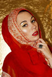 Arabian young woman. Gold make-up. Red ethnic clothes shawl hijab, accessories. stock image