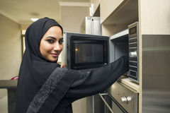 Arabian young woman in kitchen using microwave oven Stock Photo
