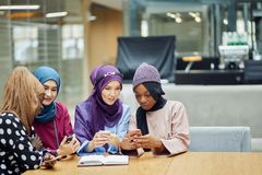 Arabian young women watching on cellphone musical video clip standing together. stock photography