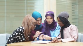 Arabian young women watching on cellphone musical video clip standing together.  stock footage