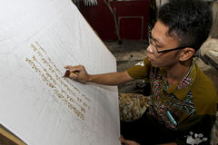 Arabic alphabet. Artists were writing the Arabic alphabet on a batik cloth in the city of Solo, Central Java, Indonesia stock photos