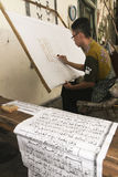 Arabic alphabet. Artists were writing the Arabic alphabet on a batik cloth in the city of Solo, Central Java, Indonesia stock images