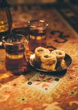 Arabic Baklava with hot black tea. Typical Middle eastern cups full of Suleimani tea served along with Bulbul`s Nest - an Arabic sweet Stock Photo
