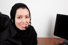 Arabic beautiful young woman with headphones. Arabic beautiful young woman in tradition scarf with headphones with microphone in the office Stock Image