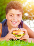 Arabic boy eating burger outdoors. Closeup portrait of cute arabic boy eating burger outdoors, lying down on green grass and enjoying picnic in the park in Stock Photo