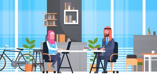 Arabic Business Man And Woman Sitting At Office Desk In Modern Coworking Space Working Together Muslim Workers In Royalty Free Stock Photo