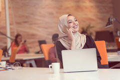 Arabic business woman wearing hijab, working in startup office. Young Arabic business woman wearing hijab,working in her startup office. Diversity, multiracial Royalty Free Stock Images