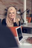 Arabic business woman wearing hijab,working in startup office. Young Arabic business woman wearing hijab,working in her startup office. Diversity, multiracial Royalty Free Stock Images