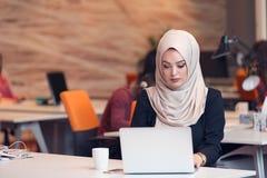 Arabic business woman wearing hijab,working in startup office. Young Arabic business women wearing hijab,working in her startup office. Diversity, multiracial Royalty Free Stock Image