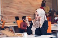Arabic business woman wearing hijab,working in startup office. Young Arabic business women wearing hijab,working in her startup office. Diversity, multiracial Stock Photo