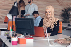 Arabic business woman wearing hijab,working in startup office. Young Arabic business women wearing hijab,working in her startup office. Diversity, multiracial Stock Photo