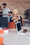 Arabic business woman wearing hijab,working in startup office. Young Arabic business women wearing hijab,working in her startup office. Diversity, multiracial Stock Photos