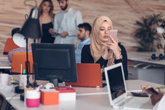Arabic business woman wearing hijab,working in startup office. Young Arabic business women wearing hijab,working in her startup office. Diversity, multiracial Stock Images