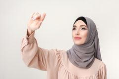 Muslim woman pointing on virtual screen, copy space. Arabic business woman working on virtual screen at white background, copy space Stock Image