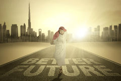 Arabic businessman runs with Better Future word Stock Images