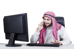 Arabic businessman talking on the cellphone. Portrait of Arabian businessman working with a computer on the table while talking on the mobile phone Stock Photography