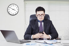 Arabic businessman typing a message on cellphone Stock Photography