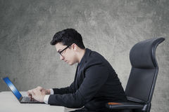 Arabic businessman uses laptop on desk. Portrait of Arabian businessman sitting on the office chair while working with laptop on the table stock photo