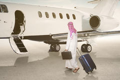 Arabic businessman walking towards the jet royalty free stock photos