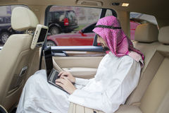Arabic businessman works with laptop in car Stock Images