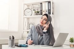 Arabic businesswoman in hijab working at office. Happy muslim businesswoman in hijab at office workplace. Smiling Arabic woman talking on smartphone, making Royalty Free Stock Photo