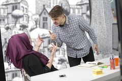 Arabic businesswoman wearing hijab receiving notification from a colleague.  Royalty Free Stock Photos