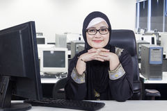 Arabic businesswoman wearing veil in office. Photo of Arabic young businesswoman sitting in the office room while smiling at the camera and wearing veil with Stock Photo