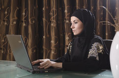 Arabic bussines lady. Traditional arabic weared lady working on laptop Royalty Free Stock Photo