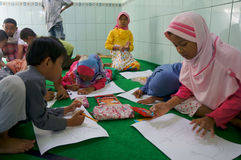 Arabic calligraphy. Children learn to write Arabic calligraphy on a mosque in the city of Solo, Central Java, Indonesia Royalty Free Stock Photo