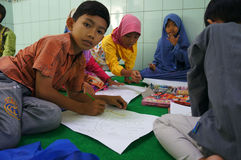 Arabic calligraphy. Children learn to write Arabic calligraphy on a mosque in the city of Solo, Central Java, Indonesia Royalty Free Stock Images