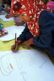 Arabic calligraphy. Children learn to write Arabic calligraphy on a mosque in the city of Solo, Central Java, Indonesia Stock Image