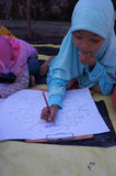 Arabic calligraphy. Children learn to write Arabic calligraphy on a mosque in the city of Solo, Central Java, Indonesia Royalty Free Stock Photos
