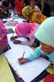 Arabic calligraphy. Children learn to write Arabic calligraphy on a mosque in the city of Solo, Central Java, Indonesia Royalty Free Stock Photography
