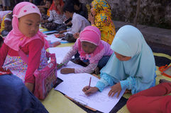 Arabic calligraphy. Children learn to write Arabic calligraphy on a mosque in the city of Solo, Central Java, Indonesia Stock Photo