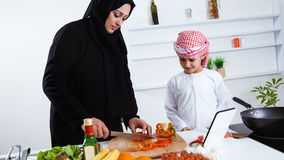 Arabic child in the kitchen with his mother Royalty Free Stock Photo