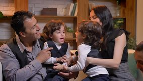 Arabic children twins battling with each other sitting on their parents in living room. Arabic children twins battling with each other sitting on their parents stock footage