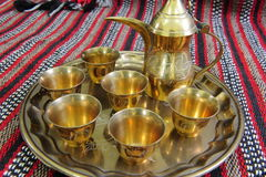 Arabic coffe pot and cups. A traditional Arabic copper coffee pot with cups on a copper serving plate royalty free stock photo