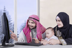 Arabic with computer and credit card. Arabian family using a computer and credit card for shopping online while sitting and looking at computer at home with royalty free stock image