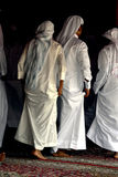 Arabic dancing. A group of Arab men, dressed in white lifting their garments as they step around in a traditional dance Royalty Free Stock Image