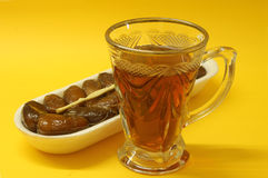 Arabic Dates fruit with tea. Fresh Arabic dates with tea on warm background Stock Photo