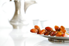 Arabic dates on a plate with Arabic coffee pot of the Bedouin. Arabic dates on a white plate with Arabic coffee pot of the Bedouin on a white background Stock Photo